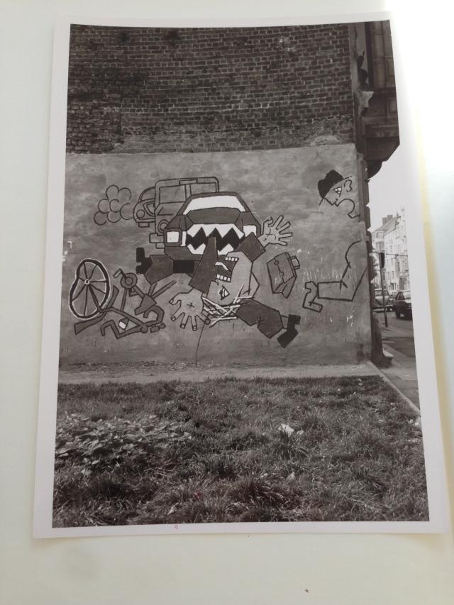 Ein Fahrradfahrer, eine Auto, ein Zuschauer. Wandbild von Klaus Paier.