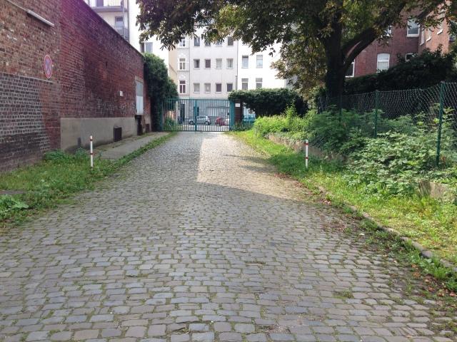 Eine breite Straße führt auf das Gelände der Tuchfabrik Aachen, errichtet 1874 ff. Das alte Pflaster ist erhalten.