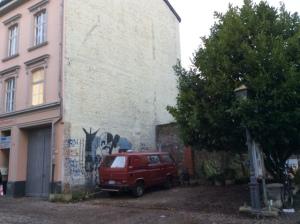 Vor dem Wandbild ist Platz für zwei Autos. Der Platz wird vermietet, aber auf den Platz würden die Vermieter sogar verzichten, wenn die Ecke ansprechend gestaltet würde. (Foto aus Sommer 2014)