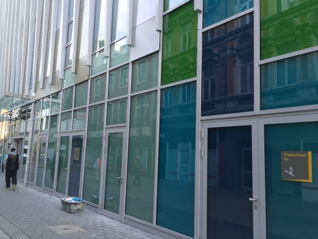 An zwei Stellen kann man das Gebäude betreten, der Rest sieht etwas abweisend aus. Schade, dass man dort die Läden nicht auch nach außen geöffnet hat, nur nach innen.
