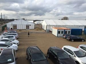 Blick auf den Parkplatz für die Mitarbeiter und einige Zelte.