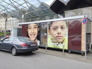 Vor dem Eurogress: Werbung für eine Com-Box, eine transportable Kiste, in der Flüchtlinge die deutsche Sprache lernen können/sollen.