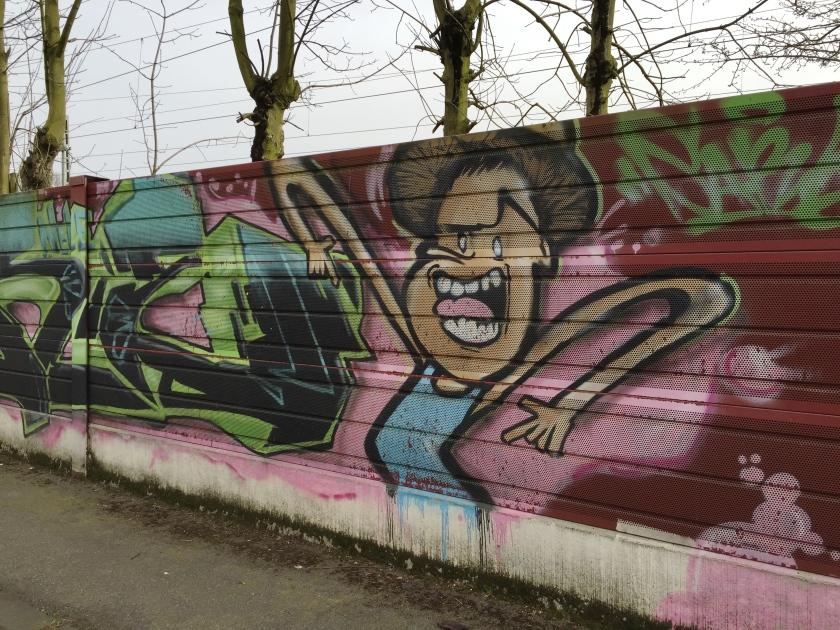 In der Bleiberger Straße gesehen (wenn ich mich richtig erinnere). Dargestellt ist eine Bloggerin, die sich über nicht-öffentliche Beratungen aufregt. ;-))